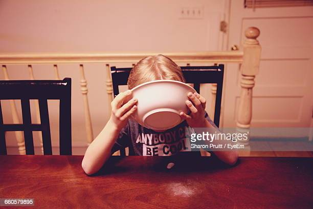 Boy Eating Food On Table At Home
