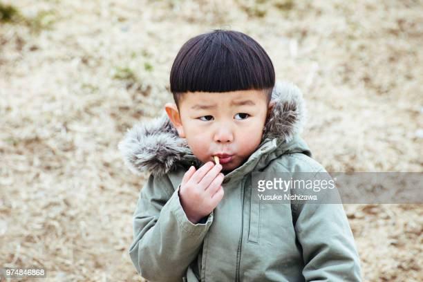 a boy eating french fries - yusuke nishizawa stock-fotos und bilder