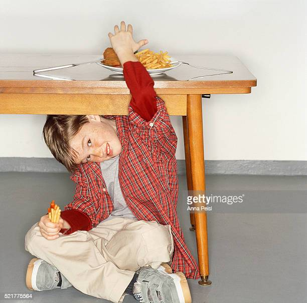 Boy Eating French Fries Under Table