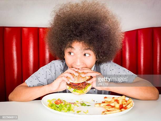 Boy (10-11) eating hamburger in American diner