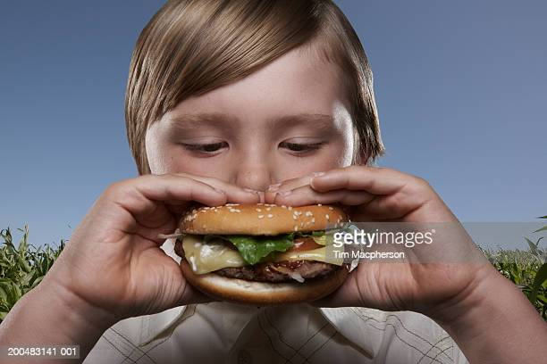 Boy (8-10) eating hamburger in countryside, close-up (Digital Composite)