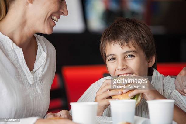 Boy eating hamburger in fast food restaurant