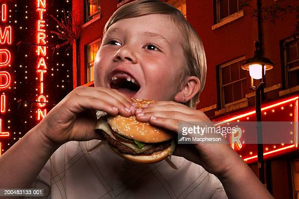 Boy (6-8) eating hamburger in neon-lit street, close-up (Digital Composite)
