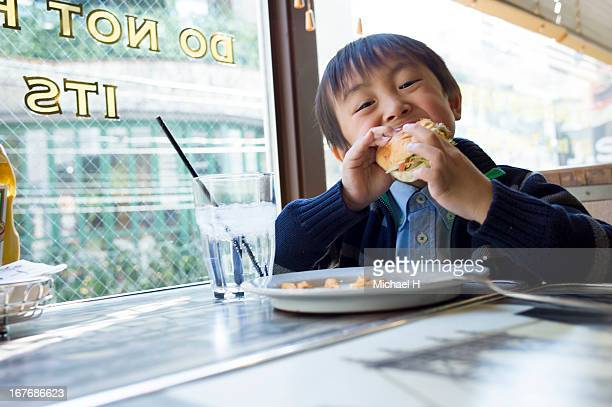 Boy eating Hamburger in restaurant