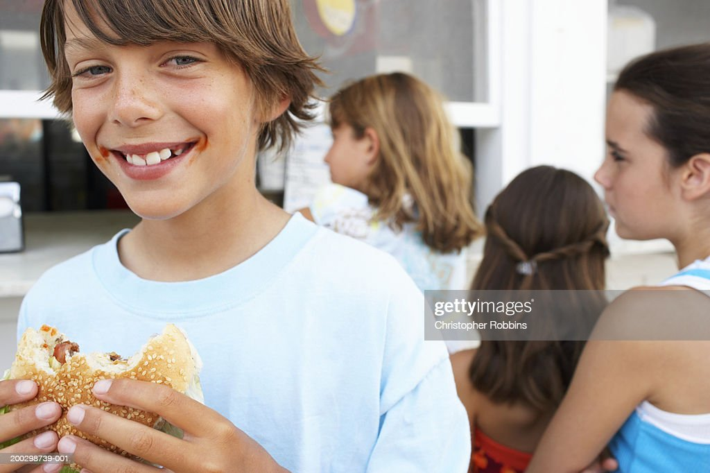 Boy (9-11) eating hamburger, portrait, three girls (9-12) queuing : Stock Photo