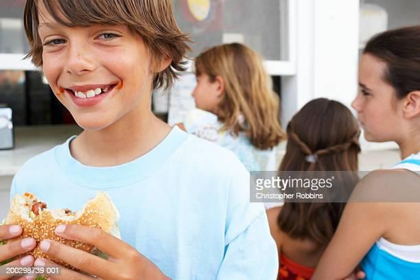 Boy (9-11) eating hamburger, portrait, three girls (9-12) queuing