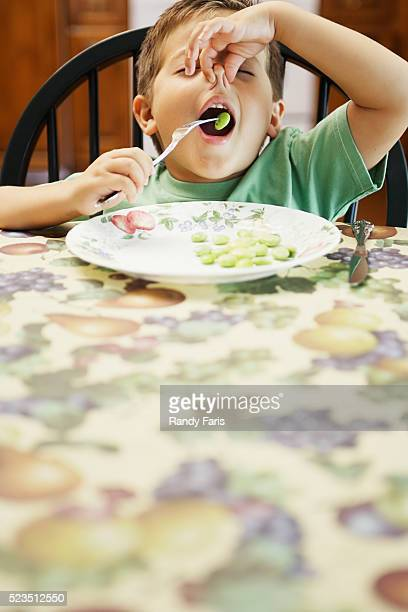 Boy Eating His Vegetables While Plugging His Nose