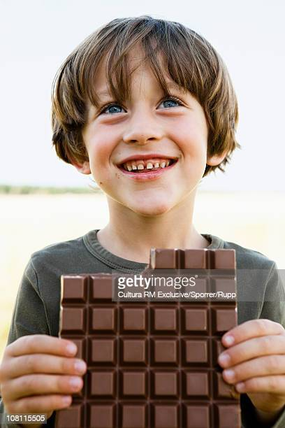 Boy eating huge piece of chocolate