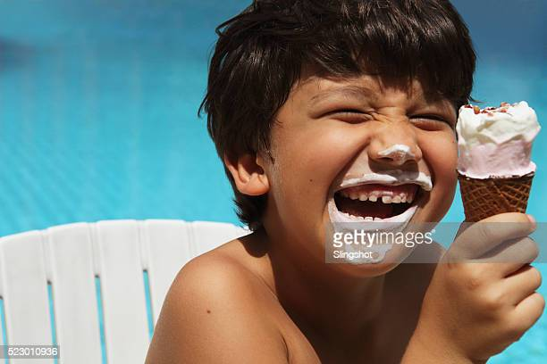 Boy (7-9) eating ice cream by swimming pool