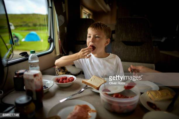 boy eating in recreational vehicle - road trip stock pictures, royalty-free photos & images