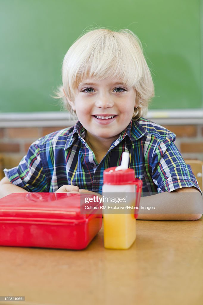 Boy eating lunch in classroom : Stock Photo