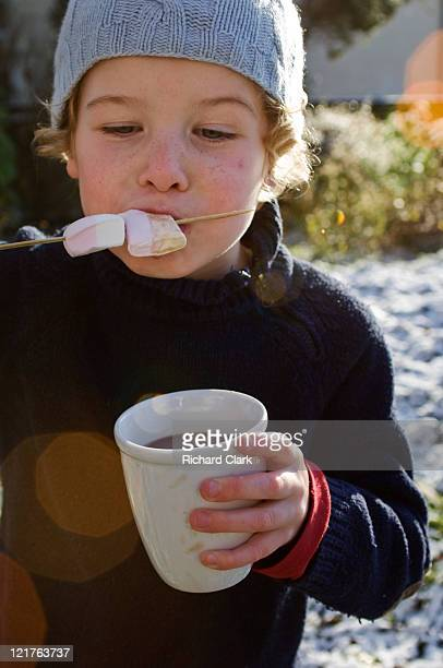 Boy eating marshmallow from skewer and holding hot chocolate