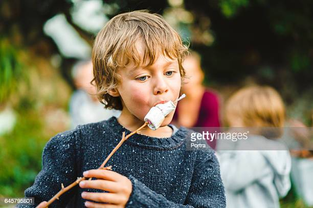 Boy eating marshmallows while looking down