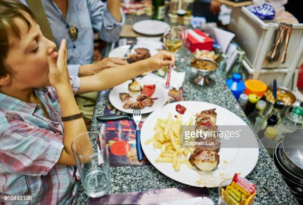 boy eating meal at restaurant, montevideo, uruguay, south america - ウルグアイ ストックフォトと画像