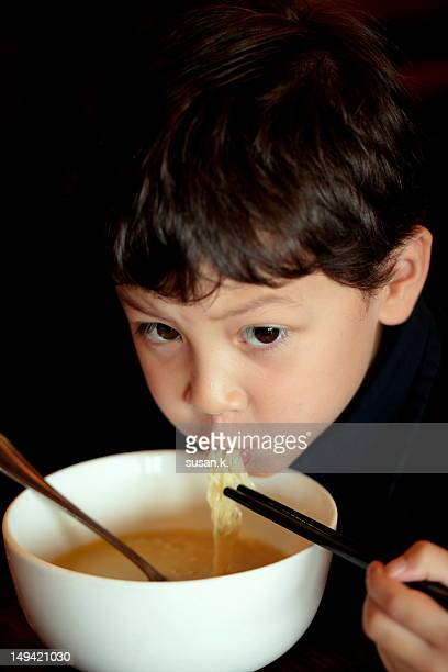 Boy eating noodle with chopstiks