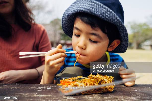Boy eating noodles outdoors