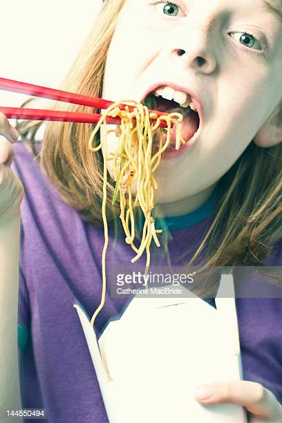 boy eating noodles with chopsticks - catherine macbride stockfoto's en -beelden