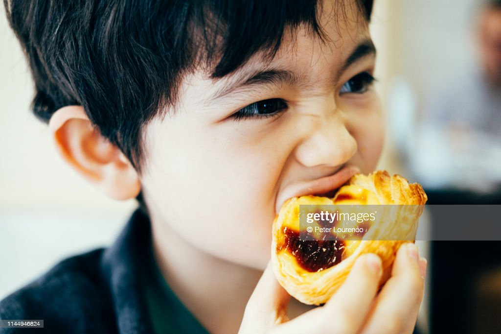 Boy eating pastel de nata : Stock Photo