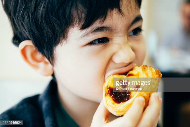 boy eating pastel de nata - peter lourenco stock pictures, royalty-free photos & images