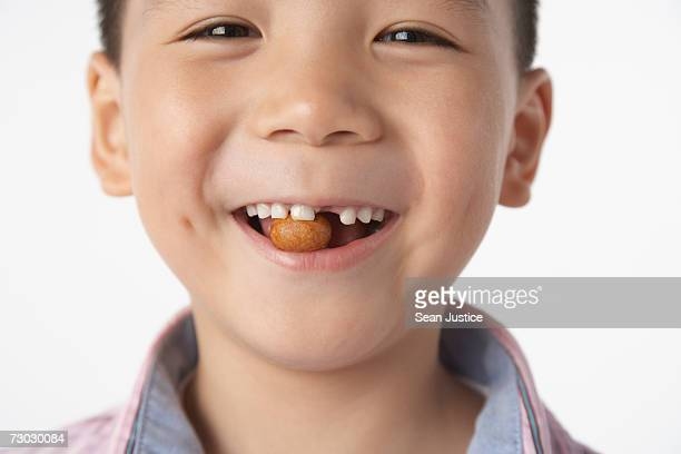 Boy (5-7) eating peanut