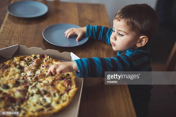 ragazzo mangia la pizza in casa - consegna a domicilio foto e immagini stock