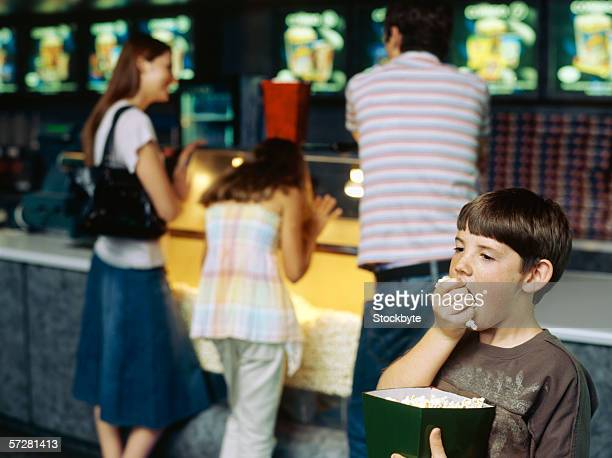Boy eating popcorn while parents and sister wait at a snack counter
