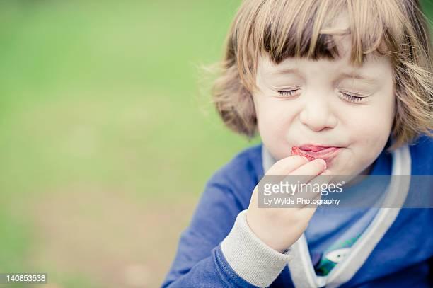 boy eating raspberries - 酸っぱい ストックフォトと画像