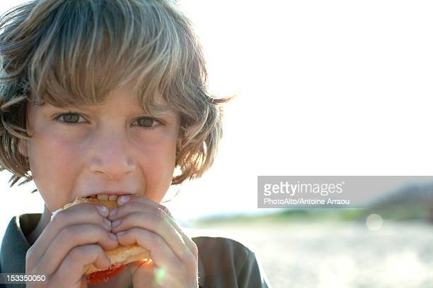 Boy eating sandwich outdoors, portrait