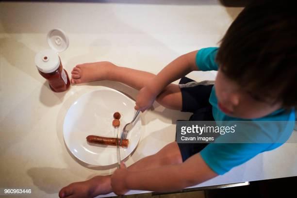 Boy eating sausage