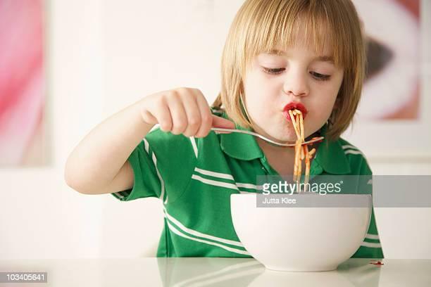 A boy eating spaghetti