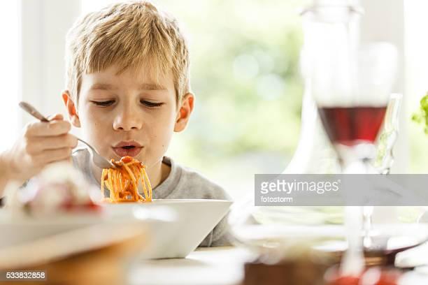 Boy eating spaghetti