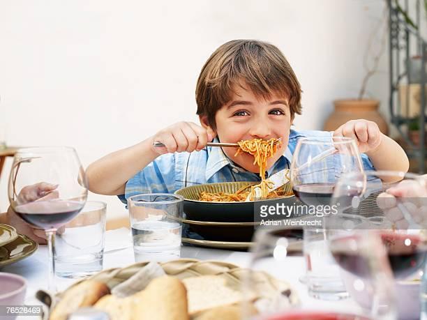 Boy (4-6) eating spaghetti, smiling, portrait