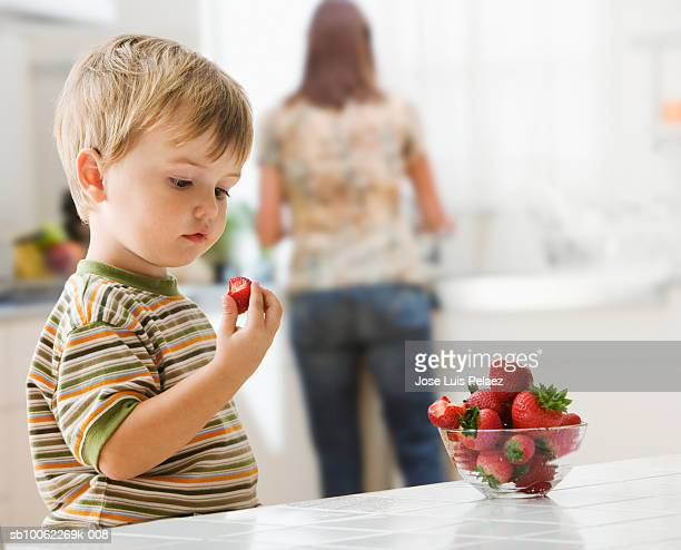 Boy (3-4) eating strawberries, while mother cooking food in background