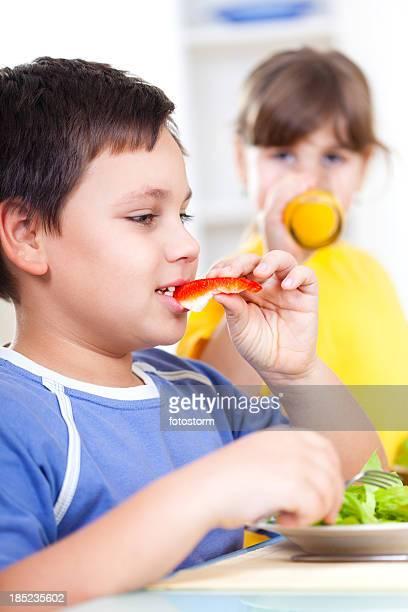 Boy eating vegetables, girl drinking juice