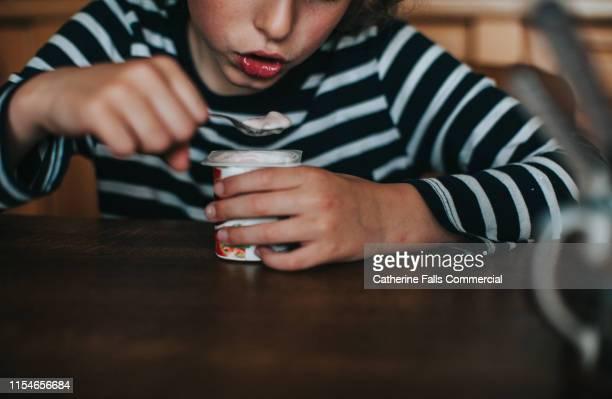 boy eating yogurt - cream stock pictures, royalty-free photos & images