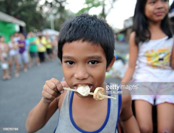 A boy eats a fishball at an informal settlers area in Manila on February 16 2011 Rising food prices have pushed about 44 million people into poverty...