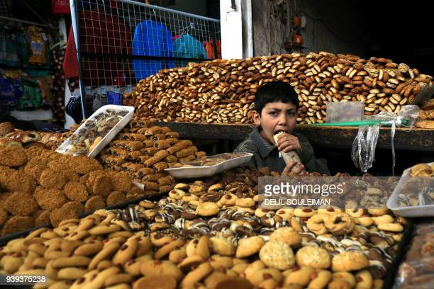 Boy eats a sandwich among pastries at the open air market in Manbij on March 28, 2018. / AFP PHOTO / Delil SOULEIMAN