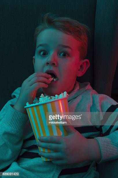 boy eats popcorn and watches scary watching movie - scary movie stock photos and pictures