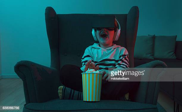 Boy eats popcorn while watching movie through VR glasses