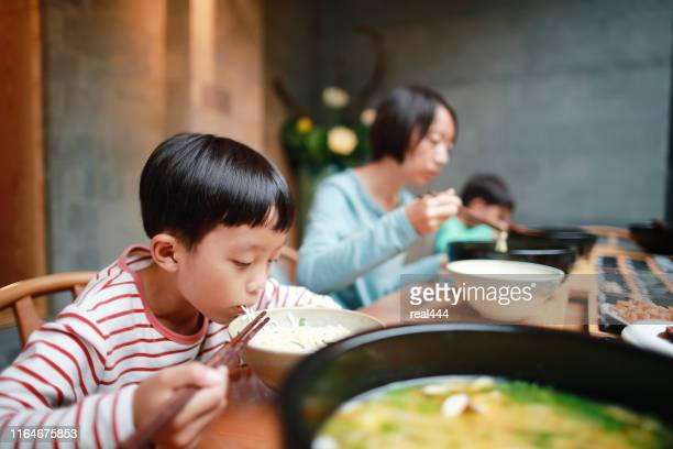 boy eats rice noodles with chopsticks - pho soup stock pictures, royalty-free photos & images