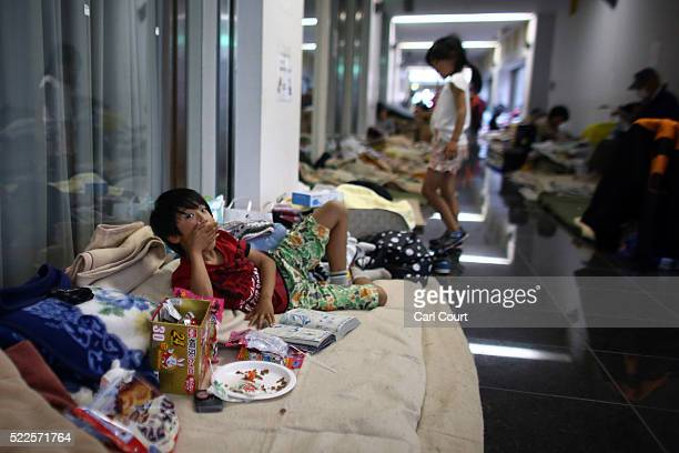 A boy eats some sweets as he shelters with his family in a gymnasium used as an evacuation centre following an earthquake on April 20 2016 in Mashiki...