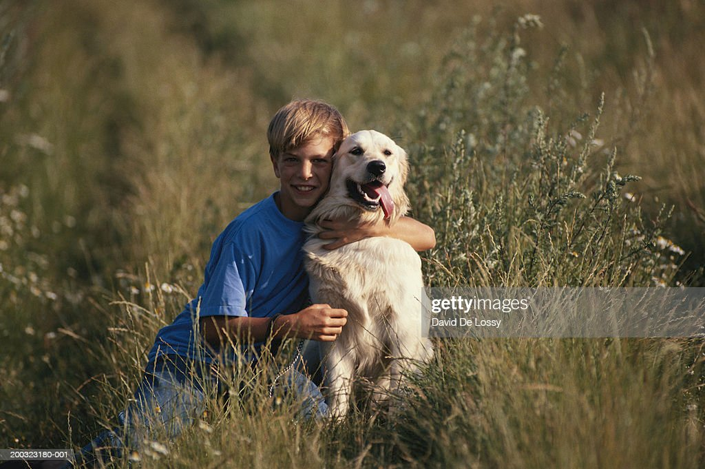Boy (10-12) embracing dog in field : Stock Photo