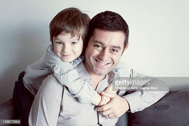Boy embracing his father, portrait