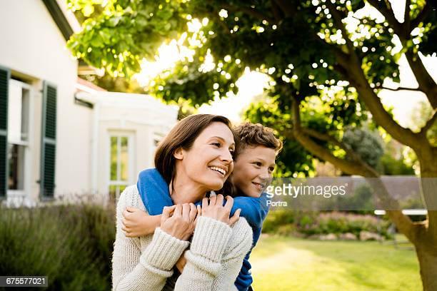 boy embracing mother outside house in yard - mamma e figlio foto e immagini stock