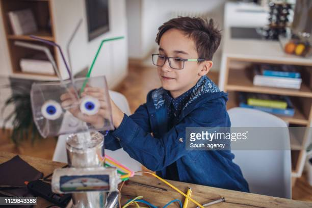 boy engineer constructing a robot at home - child prodigy stock pictures, royalty-free photos & images