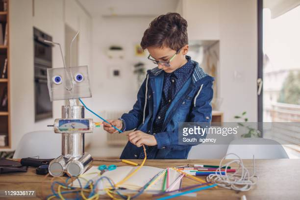 boy engineer making a robot at home - stem assunto imagens e fotografias de stock