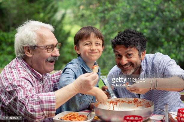 boy enjoying a meal together with father and grandfather - italian culture stock pictures, royalty-free photos & images