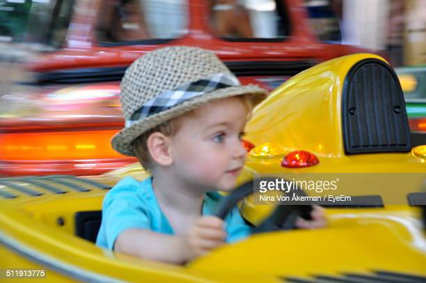 boy enjoying bumper car ride at amusement park - land vehicle stock pictures, royalty-free photos & images