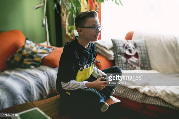 boy enjoying game console at home.natural light - children only stock pictures, royalty-free photos & images