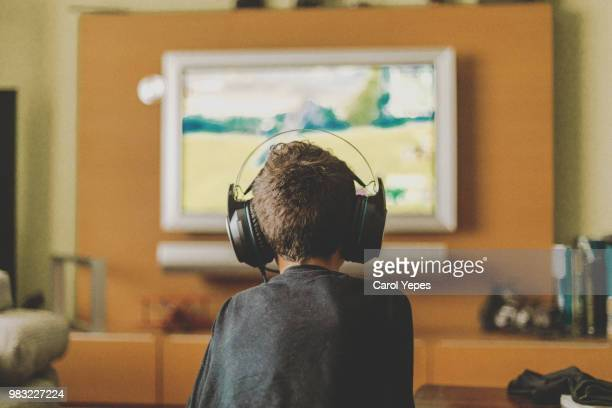 boy enjoying game console at home.rear view - verslaving stockfoto's en -beelden